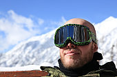 Man Snowboarder or Skier with Goggles at Ski Resort