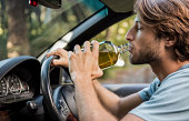 Man driving car while drinking alcohol