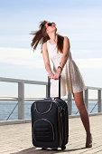 Beautiful woman girl sea mooring suitcase on a pier