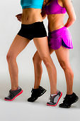 Two slim young woman showing leg muscles after pilates workout