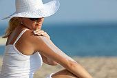 Woman applying Suntan Lotion at the beach