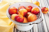 fresh nectarines and plums in colander
