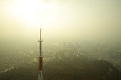 Cell tower in smog overlooking urban cityscape
