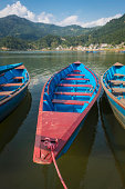 Colourful wooden rowing boats on mountain lake resort