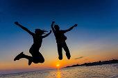 Joy, Silhouette Beautiful couple are having fun jumping over sunset