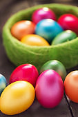 Colorful Easter Eggs in Basket on rustic wood