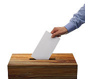 Male placing his voting envelope into a wooden ballot box
