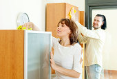 Positive couple wiping the dust from  furniture
