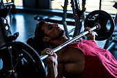 Man on an incline bench doing bench presses