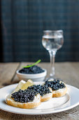 Sandwiches with black caviar and glass of vodka