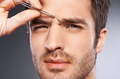 Man tweezing eyebrows.