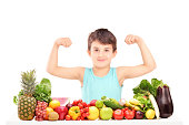 Healthy child showing his muscles and sitting on a table