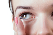 Inserting a contact lens in female eye
