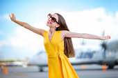 Young woman dressed in yellow dress simulating flight with hands