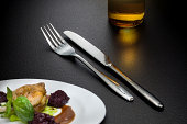 bottle of beer, knife and fork on table