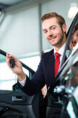 Young man or auto dealer in car dealership