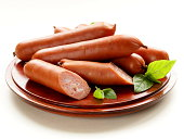 delicious smoked sausages on a wooden plate with basil leaves