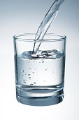 Water is pouring into the glass. With clipping path