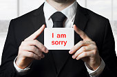 businessman holding sign i am sorry