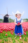 Little girl wearing Dutch costume in tulips field with windmill