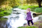 Beautiful baby girl walking at river shore on autumn day