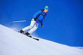 Mid adult women snow skier skiing on sunny ski resorts