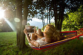 Woman on hammock at sunset taking picture with digital tablet