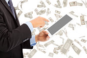 business man touching tablet with money rain background