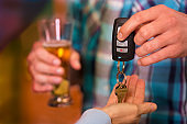 Drinking and Driving.  Man gives car keys to friend.  Beer.