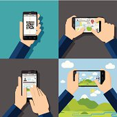 Hands holding touchscreen smartphones with applications on screens