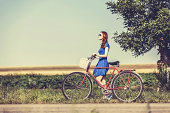 Redhead girl with bicycle on country road.