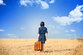 Brunette girl  withsuitcase on wheat field.