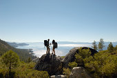 Hiking Couple Standing On Rock At Coast
