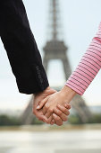 Couple Holding Hands Against Blurred Eiffel Tower