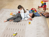 Children Lying On Rug At Home