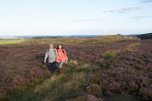 Senior Couple Hiking Across Moorland Covered With Heather
