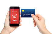 female hands holding phone and credit card making online purchase