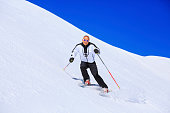 Mature men snow skier skiing on sunny ski resorts