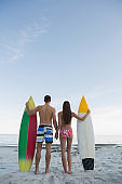 Beautiful couple holding surfboards on the beach