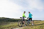 Senior couple riding mountain bikes