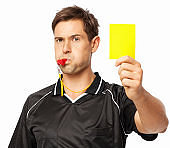 Soccer Referee Whistling While Showing Yellow Card