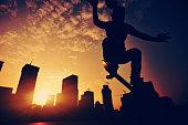 skateboarding woman jumping at  sunrise