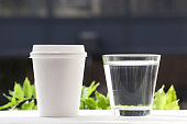 Disposable coffee cup and glass of water.