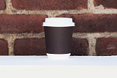 Disposable coffee cup with brick wall in background.