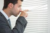 Handsome calm businessman spying through roller blind