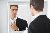 Serious handsome bridegroom looking in mirror