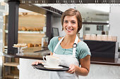 Waitress holding tray with cappuccinos