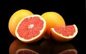 Studio shot sliced three grapefruits isolated black