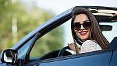 beautiful smiling woman in a convertible car