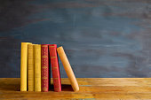 row of books, on blackboard background, free copy space